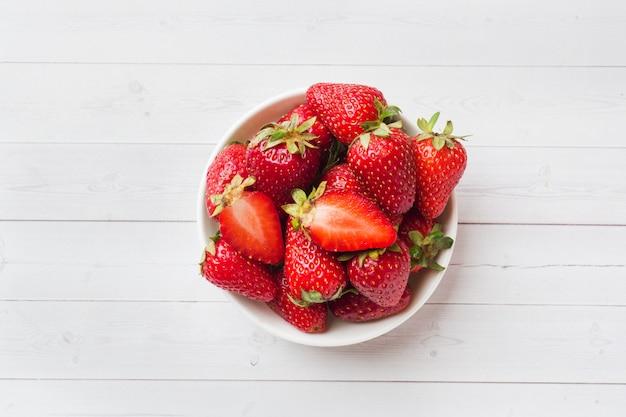 Frische erdbeeren in einer keramischen platte auf einer weißen tabelle. kopieren sie platz.