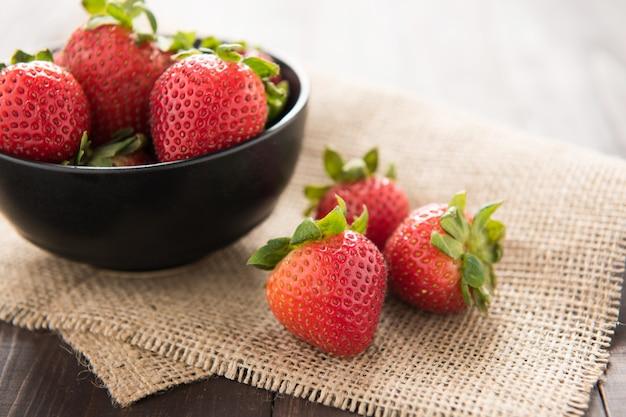 Frische erdbeeren in einer schüssel auf holz