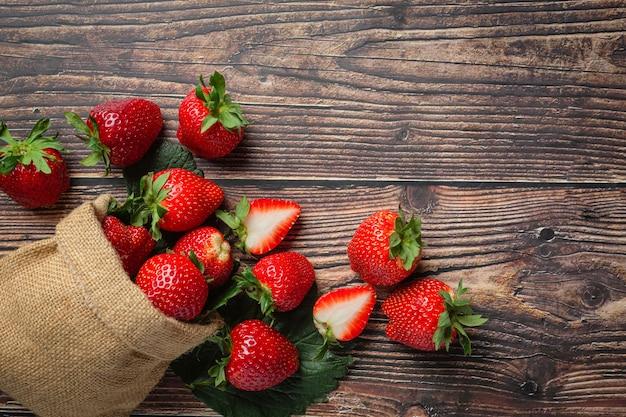 Frische erdbeeren in einer schüssel auf holztisch