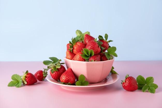 Frische erdbeeren in einer schüssel auf rosa hintergrund. sommer essen. platz kopieren