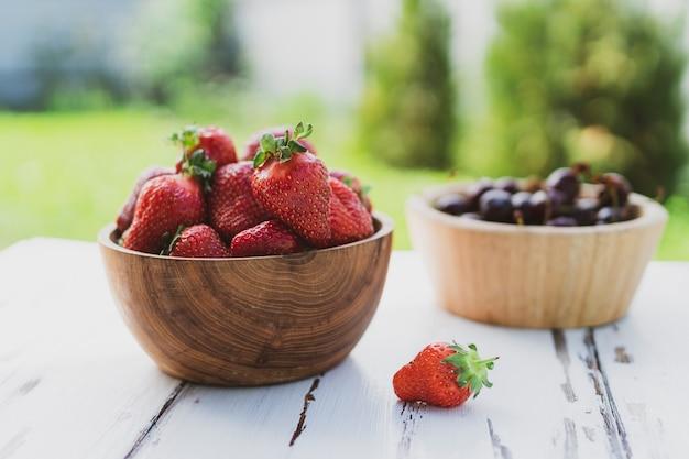 Frische erdbeeren in holzschale auf grünem hintergrund