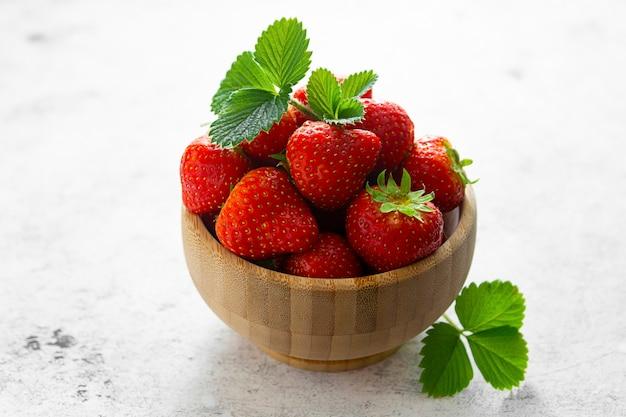 Frische erdbeeren in holzschale mit grünen blättern