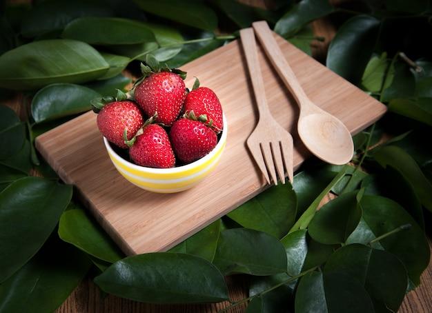 Frische erdbeeren und saft auf holztisch. flach legen.