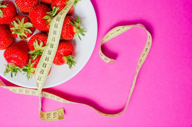 Frische erdbeeren und zentimeterband. das konzept der richtigen ernährung. diätetische lebensmittel.