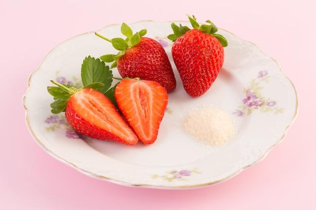 Frische erdbeeren und zucker auf altem teller auf rosa hintergrund