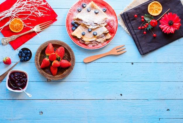 Frische erdbeerpfannkuchen oder -crepes mit beeren und schokolade