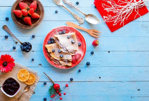 Frische erdbeerpfannkuchen oder crepes mit beeren und schokolade