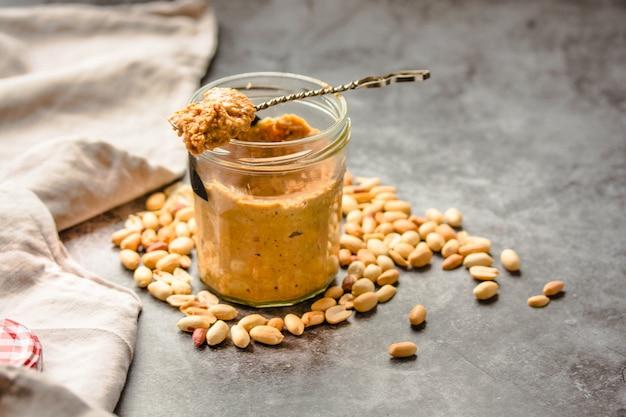 Frische erdnuss verbreitet im glas und löffel und zerstreute erdnüsse auf grau