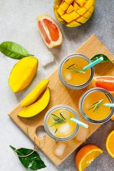 Frische erfrischende sommergetränke multifruit drinks aus zitrus und mango mit eis
