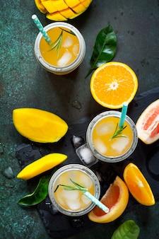 Frische erfrischende sommergetränke multifruit-getränke aus zitrus und mango mit eis-smoothies
