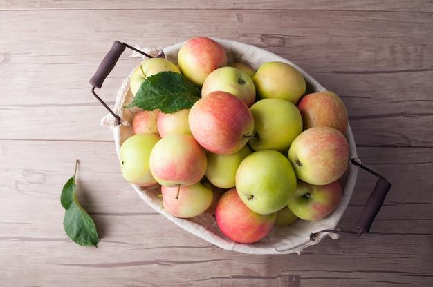 Frische erntende äpfel im korb auf holztisch