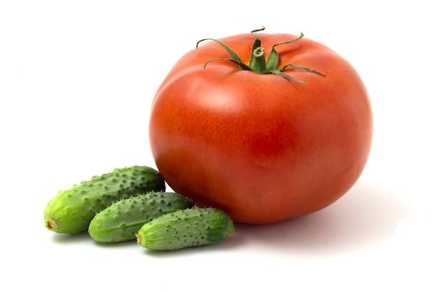 Frische essiggurken und große rote tomate lokalisiert auf weißem hintergrund.