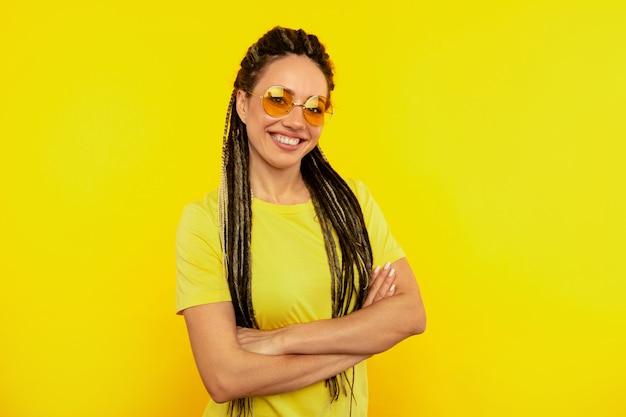 Frische farbe. glückliche frau mit langen dreadlocks, die auf dem gelben hintergrund aufwerfen.