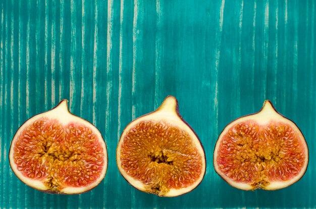 Frische feigen auf hellem blau oder türkis hölzern in einer reihe. ansicht von oben platz kopieren. sommer trägt konzept früchte