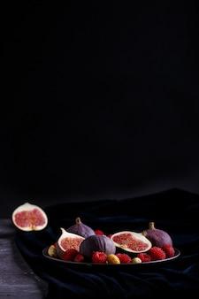 Frische feigen, erdbeeren und himbeeren auf blauer platte auf schwarzem konkretem und blauem samtgewebe. seitenansicht, selektiver fokus, zurückhaltend