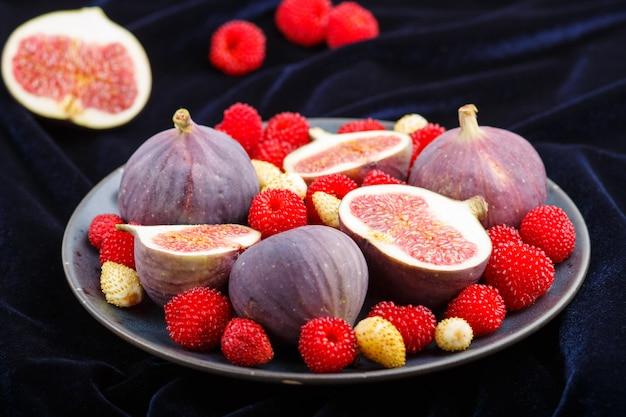 Frische feigen, erdbeeren und himbeeren auf blauer platte