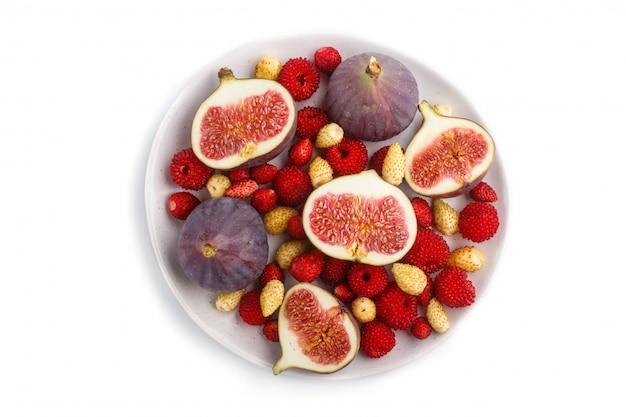 Frische feigen, erdbeeren und himbeeren auf der weißen platte lokalisiert