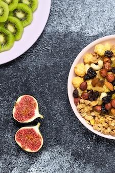 Frische feigen, kiwischeiben und frühstückszerealien, müsli mit rosinen und nüssen