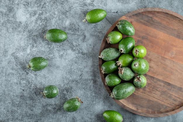Frische feijoa-früchte auf holzteller.
