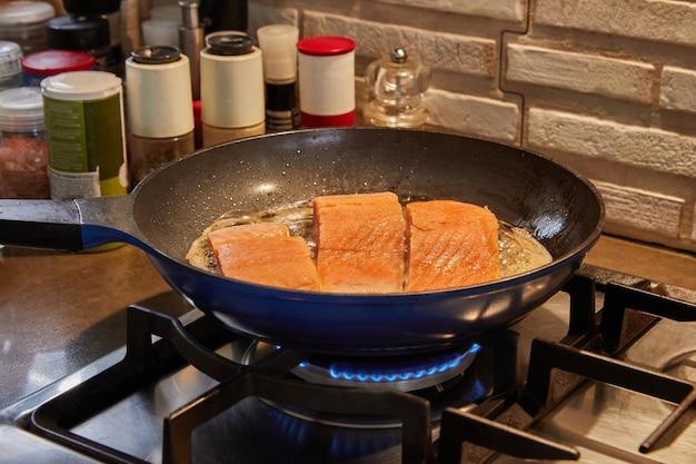 Frische filets von salomon-fisch werden in einer pfanne auf einem gasherd gebraten.