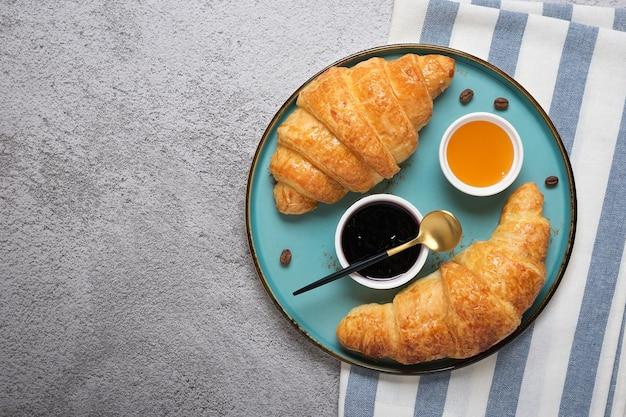 Frische französische croissants mit blaubeermarmelade, honig und einer tasse kaffee