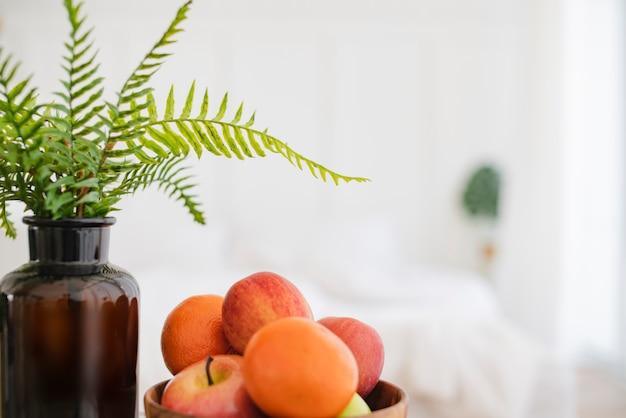Frische frucht auf hölzerner schüssel auf gesundem lebensstil des weißen bettmorgens