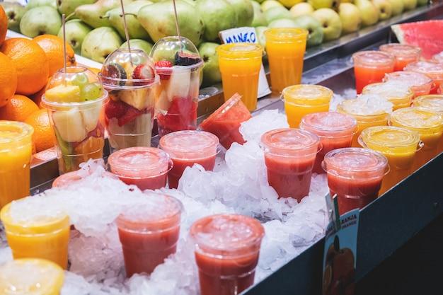 Frische fruchtcocktails und scheiben der verschiedenen früchte in einem glas auf einem kostenzähler im markt