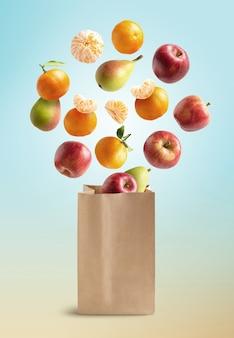 Frische früchte fliegen aus einer recycelbaren papiertüte