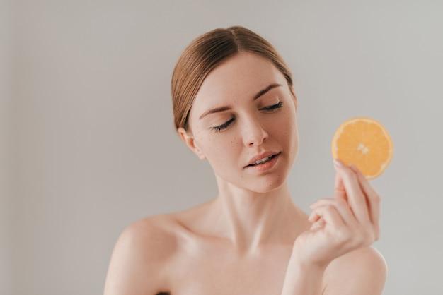 Frische früchte machen ihre haut perfekt. attraktive junge frau, die orangenscheibe hält und wegschaut, während sie gegen den hintergrund steht