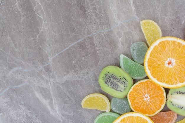 Frische früchte mit süßen marmeladen auf marmorhintergrund.