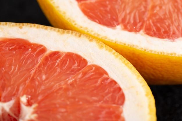 Frische früchte saftig ausgereifte reife stücke der leckeren grapefruit isoliert auf dunkel