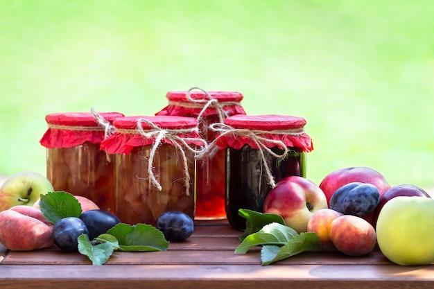 Frische früchte und selbst gemachte gläser stau auf holztisch in unscharfem natürlichem garten. konserven von pfirsichen, nektarinen, pflaumen, äpfeln
