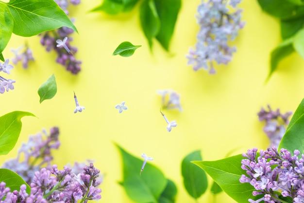 Frische frühlingsbeschaffenheit von fliederblumen mit fliegenden waffeltassen für eiscreme im flug. frühlingsblühkonzept