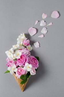 Frische frühlingsrosen im waffelkegel. schöner romantischer hintergrund in der flachen lageart.