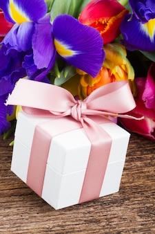 Frische frühlingstulpen und iris auf holz mit geschenkbox