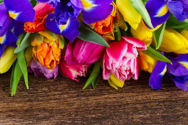 Frische frühlingstulpen und iris auf holz