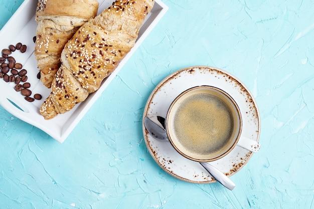 Frische ganze kornhörnchen und -tasse kaffee auf blauem hintergrund. platz kopieren, draufsicht