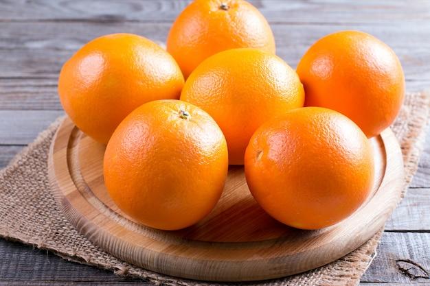 Frische ganze orangen auf einem schneidebrett