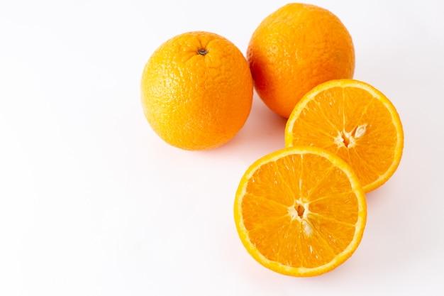 Frische ganze orangen von oben aus der nähe saftig und sauer auf den exotischen zitrusfarbenfrüchten des weißen hintergrunds