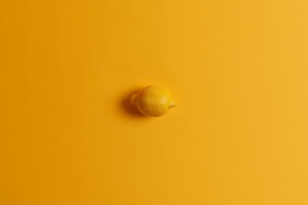 Frische ganze saftige saftige gelbe zitrone in einer farbe mit hintergrund. tropische zitrusfrüchte. monochromer schuss. quelle von vitaminen. zutat für die herstellung von limonade. gesundes essen, esskonzept