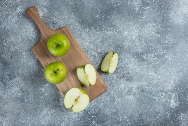 Frische ganze und geschnittene äpfel auf holzbrett.
