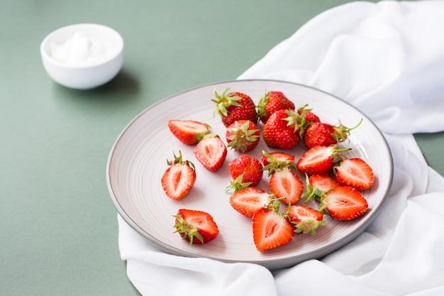 Frische ganze und geschnittene erdbeeren auf einem teller und sauerrahm in einer schüssel auf einem grünen tisch.