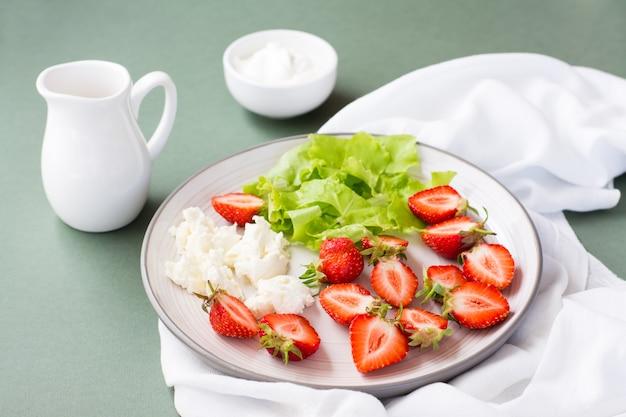 Frische ganze und geschnittene erdbeeren, hüttenkäse und salat auf einem teller und sauerrahm in einer schüssel auf einem grünen tisch.