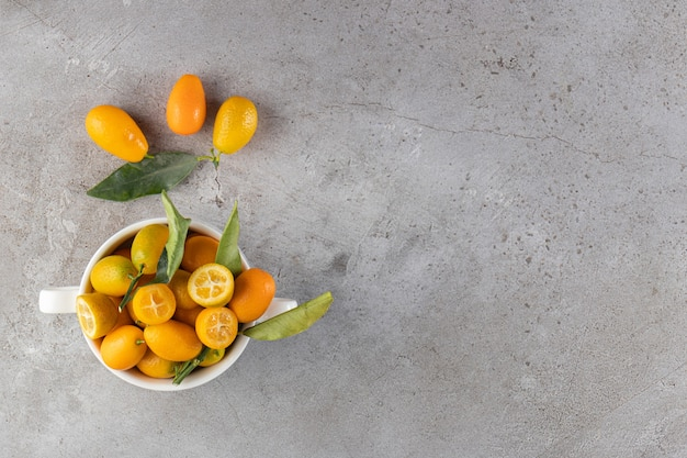 Frische ganze und geschnittene zitrusfrüchte mit blättern auf einer schüssel.