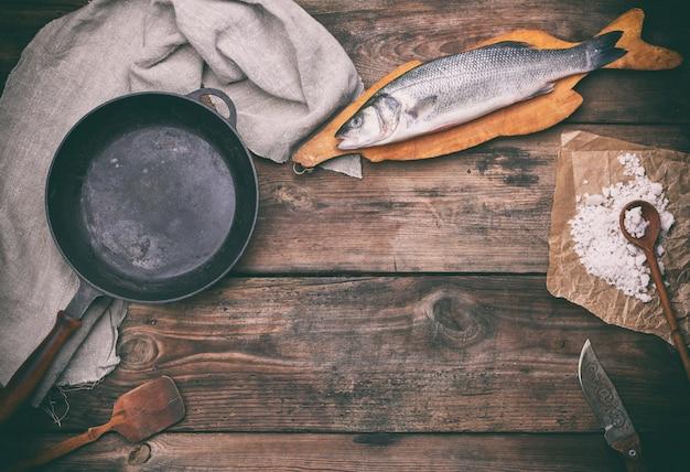 Frische ganze wolfsbarschfische auf braunem schneidebrett