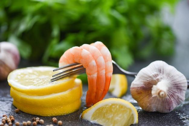 Frische garnelen auf der gabel, die auf gekochten abgezogenen garnelen der plattenmeeresfrüchte gedient wurde, kochten mit gewürzzitrone