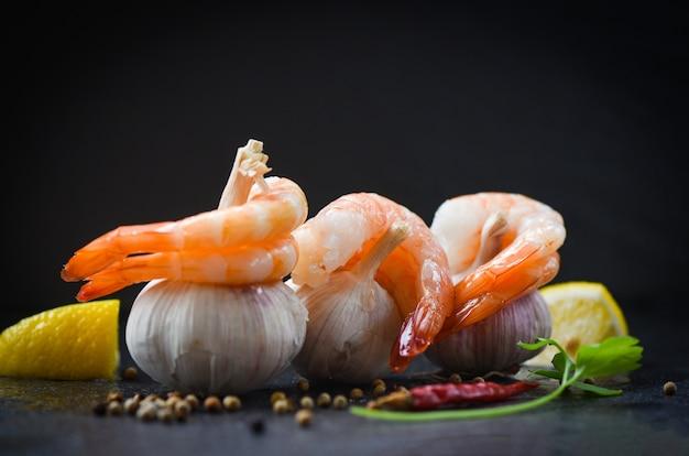 Frische garnelen auf knoblauch, serviert auf gekochten, geschälten garnelen auf meeresfrüchten