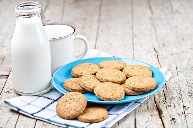 Frische gebackene haferplätzchen auf blauer keramischer platte auf leinenserviette, flasche milch und keramischer schale