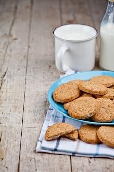 Frische gebackene haferplätzchen auf blauer keramischer platte auf leinenserviette und schale milch.