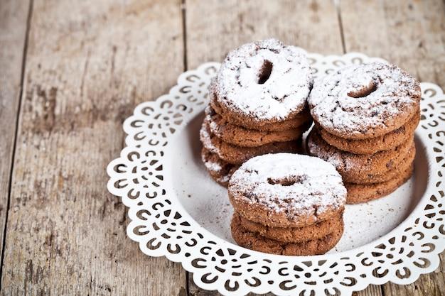 Frische gebackene schokoladensplitterplätzchen mit zuckerpulverhaufen auf rustikalem holztischhintergrund weißen plateon